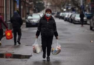 Một phụ nữ đi bộ trên đường phố Vũ Hán sau khi từ chợ về ngày 26/1. Ảnh:AFP.