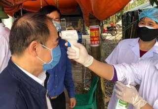 """PGS.TS Trần Đắc Phu - nguyên Cục trưởng Cục Y tế Dự phòng (Bộ Y tế), cố vấn Trung tâm đáp ứng khẩn cấp sự kiện y tế công cộng Việt Nam được đo thân nhiệt tại """"tâm dịch"""" ở Vĩnh Phúc. Ảnh: Hà Anh Đức"""